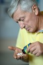 Elderly man treated by medicines on a gray background Stock Photos