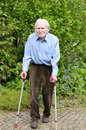 Elderly man using forearm crutches to walk with casual clothes as a mobility aid on the cobblestones of a footpath in a green park Stock Photo