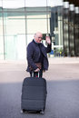 Elderly man waving goodbye as he makes his way to the departure terminal with his suitcase at the end of his holiday Royalty Free Stock Image