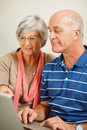 An elderly man and woman using a computer laptop Stock Images
