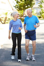 Elderly man and younger woman jogging men women Royalty Free Stock Image