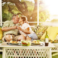 Elderly married couple kissing photo of on patio with wine glasses Royalty Free Stock Images
