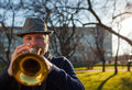 An elderly musician plays in the street on a trumpet Royalty Free Stock Photo