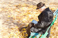 Elderly one legged man sitting reading in the park handicapped on a wooden bench on a sunny autumn day with his crutches alongside Stock Photos