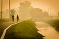Elderly people in countryside bike road near little brook in fog and bridge location Stock Photos