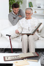 Elderly person looking at photos with son Stock Images