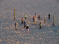 Elderly playing volleyball on isolated beach people at sunset long shadows Royalty Free Stock Photos
