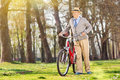 An elderly pushing his bike in the park outdoors Royalty Free Stock Images