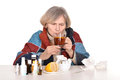 Elderly sick woman drinks portrait of an over a white background Stock Photography