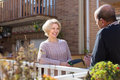 Elderly spouses in patio happy women with horticultural sundry and aged men drinking tea Stock Photography