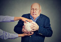 Elderly upset scared business man holding piggy bank trying to protect his savings from being stolen