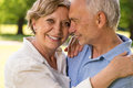 Elderly wife and husband cuddling outdoors smiling Royalty Free Stock Photography