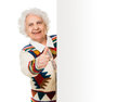 Elderly woman alongside of ad board over white background Royalty Free Stock Images