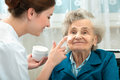 Elderly woman is assisted by nurse at home assists an women with skin care and hygiene measures Royalty Free Stock Image