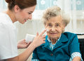 Elderly woman is assisted by nurse at home assists an women with skin care and hygiene measures Stock Images