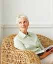 Elderly woman on a cane chair with a book Stock Image