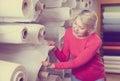 Elderly woman choosing interesting fabric