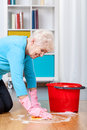 Elderly woman cleaning floor Royalty Free Stock Photo