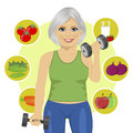 Elderly woman with dumbbells and variety of healthy vegetables