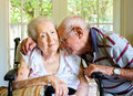 Elderly woman eighty plus year old women in a wheel chair in a home setting with her husband Royalty Free Stock Image