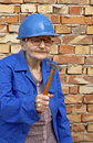 Elderly woman with a hammer holding construction background Stock Images