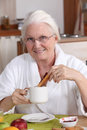 Elderly woman having breakfast her Stock Photos