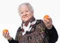 Elderly woman holding two tangerines i Stock Photo