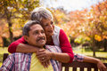 An elderly woman hugs her husband sitting on the bench Royalty Free Stock Photo