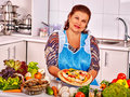 Elderly woman kitchen preparing a pizza mature at near lot of vegetable she is happy Royalty Free Stock Photography