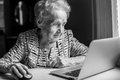 An elderly woman with a laptop.
