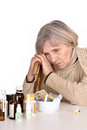 Elderly woman looking at pills portrait of an sick over a white background Stock Photography