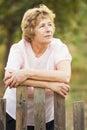 Elderly woman near a wicket to the garden Royalty Free Stock Photos