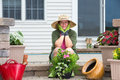 Elderly woman pausing while potting up plants smiling attractive on the steps of her patio in her wide brimmed sunhat and Stock Photography