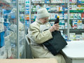 an elderly woman in the pharmacy an staring at label on bottle Royalty Free Stock Photo