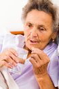 Elderly woman with pills lady taking glass of water at home Stock Photography
