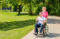 Elderly woman in pink blouse pushes wheel chair Royalty Free Stock Photo