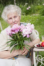 Elderly woman with pink flowers Royalty Free Stock Image