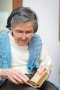 Elderly woman praying and holding a bible between palms in her home Stock Photography
