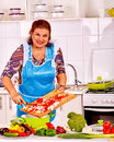 Elderly woman prepares food in the kitchen happy blue apron preparing dinner at Royalty Free Stock Photography