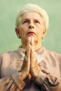 Elderly woman religion portrait serious senior caucasian woman hands joined praying god green background Stock Images