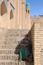Elderly woman sitting in the shade on the stairs uzbekistan Stock Image