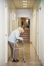 Elderly woman standing in passageway full length of a tired with walker hospital Stock Photos
