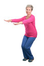 Elderly woman tracksuit doing squats cheerful gymnastic exercises vigorously Stock Photo
