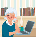 Elderly woman using a laptop an smiles at the camera while sitting at Royalty Free Stock Photography