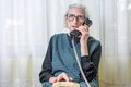 Elderly woman using the phone indoors years old Stock Images