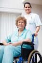 Elderly woman on a wheelchair being assisted Royalty Free Stock Photography
