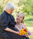 Elderly woman women get flowers from her grandchild Royalty Free Stock Image