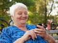 The elderly woman writes the message in phone Royalty Free Stock Photos