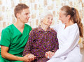 Elderly woman with the young doctors Stock Photo