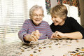 Elderly Woman and Younger Woman Doing Puzzle Royalty Free Stock Photo